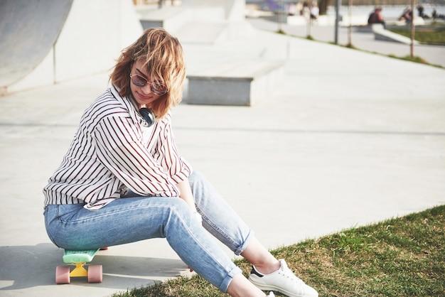 Una bella ragazza si sta divertendo nel parco e in sella a uno skateboard.