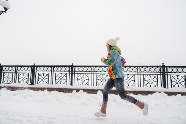 A beautiful young girl is jogging on a frosty and snowy day. sports, healthy lifestyle.