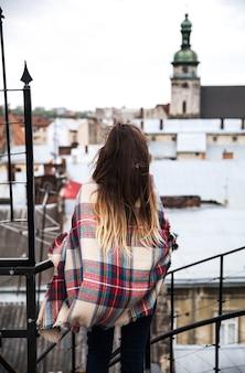 Красивая молодая девушка стоит на крыше и смотрит на город