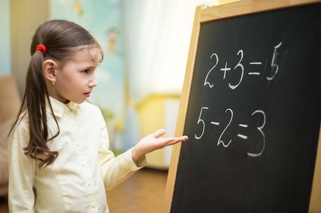 Beautiful young girl is teaching at home on blackboard