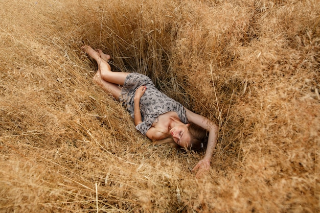 Beautiful young girl  is on wheat field in sunny day. an seductive girl with long light  hair walk in the wheat field happy girl in  field with spikelets landscape. weekend outdoors in summer.