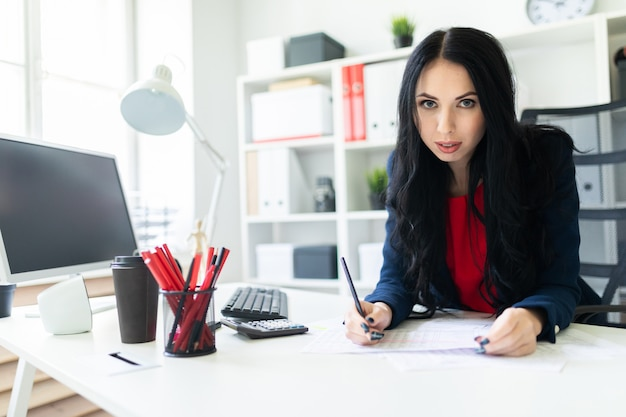 Beautiful young girl is working with documents in the office at the table and is holding a pencil in her hand.