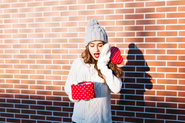 Beautiful young girl in knitted hat and gloves on wall  outside. she holds open present in hands, looks surprised.