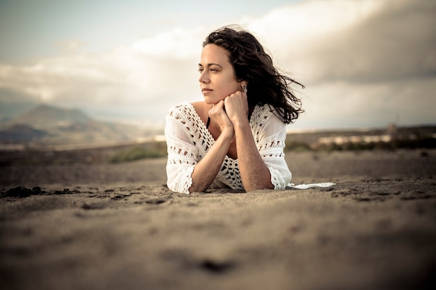 Красивая молодая девушка легла на пляж, наслаждаясь ветром, погодой и свободой