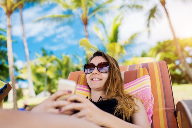 Beautiful young girl laying on a sun bed and texting on her smart phone. relaxing on a vacation, on a beautiful island.