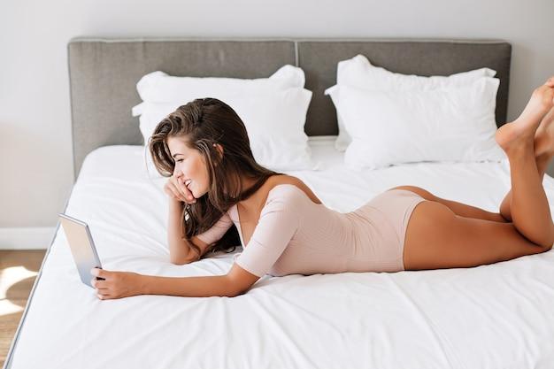 Bella ragazza che pone sul letto bianco al mattino. lei sorride per tamponare le mani.