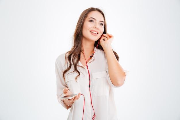 흰 벽에 격리된 이어폰과 스마트폰으로 음악을 듣는 아름다운 소녀