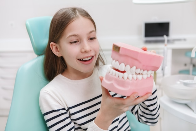 Красивая молодая девушка, глядя на модель большой челюсти, сидя в стоматологическом кресле
