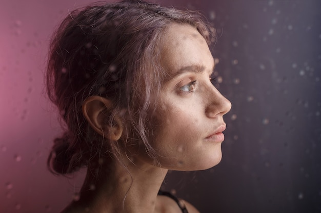 Beautiful young girl looks away on purple background. blurry drops of water run down the glass in front of her face