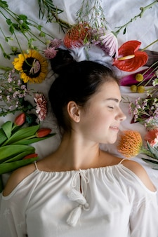 Beautiful young girl lying in a bed with flowers