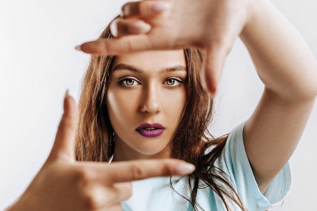 아름 다운 젊은 여자는 격리 된 회색 배경에 그녀의 손으로 프레임을 만든다.