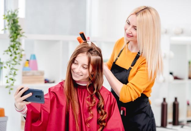 Красивая молодая девушка, делая селфи с парикмахером во время процесса прически. кудри на длинные волосы