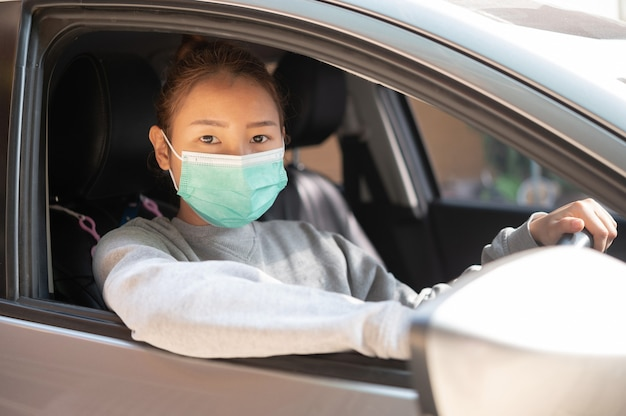 Beautiful young girl in a mask sitting in a car,