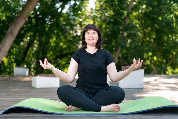 아름 다운 소녀 녹색 요가 매트에 앉아 공원에서 명상. 건강한 생활. 로터스 위치.