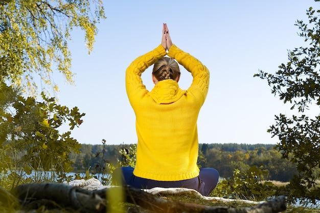 Красивая молодая девушка медитирует в осеннем парке. женщина медитирует в лесу.