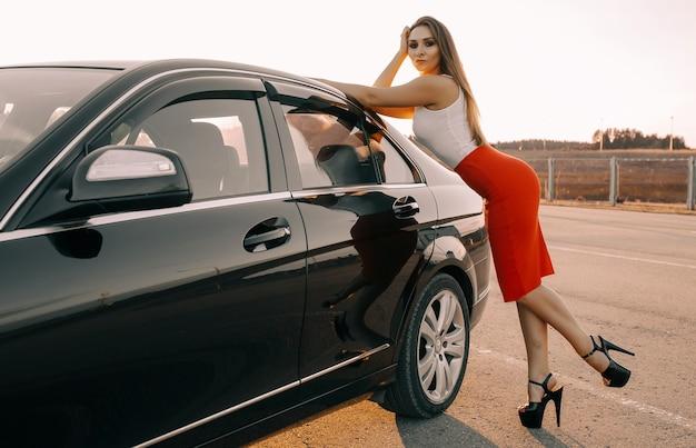 빈 주차장에서 일몰 태양에서 저녁에 차 근처에 아름 다운 젊은 여자