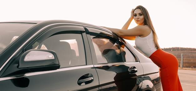 Красивая молодая девушка возле машины вечером на закате солнца на пустой парковке
