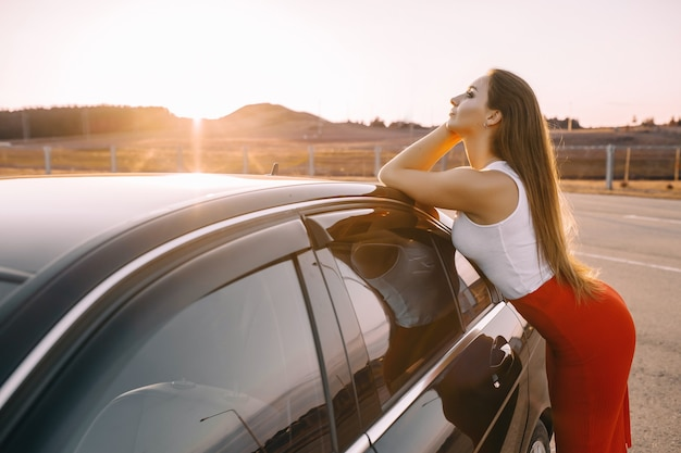 Beautiful young girl near a car in the evening in the sunset sun in an empty parking lot