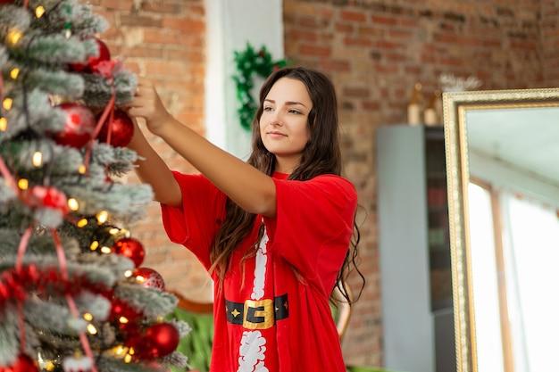 Beautiful young girl near the christmas tree