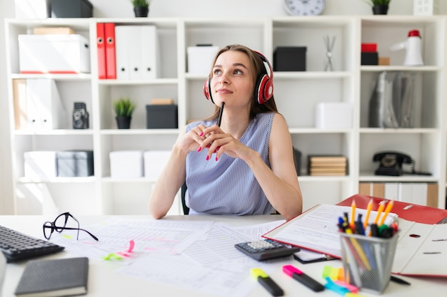 Beautiful young girl in the office sits at a table in red headphones and holds a pencil in hands.