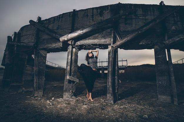 Красивая молодая девушка на плотине в высохшем озере в черной развевающейся юбке