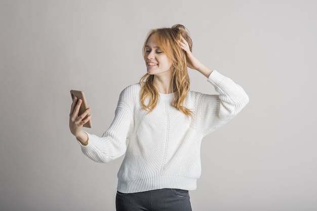 スタジオで白い背景の美しい少女がスマートフォンで自分撮りをします
