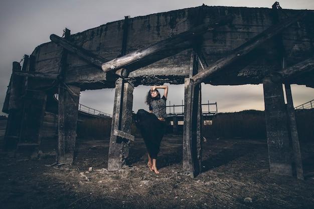黒い揺れるスカートの干上がった湖のダムの背景に美しい少女
