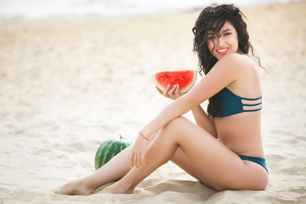 Красивая молодая девушка на пляже, загорая
