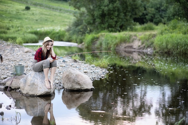Красивая молодая девушка на природе у реки с удочкой