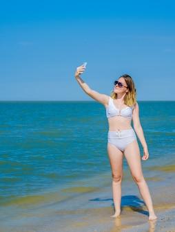 スマートフォンでポーズをとって自分撮りをしている水の近くの海のビーチで美しい少女