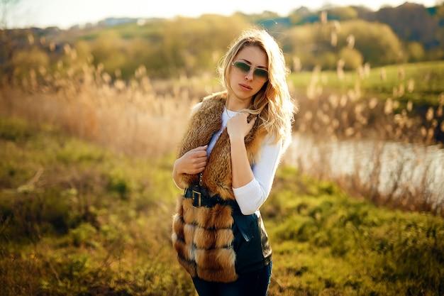 Красивая молодая девушка на улице в меховой жилет и солнцезащитные очки
