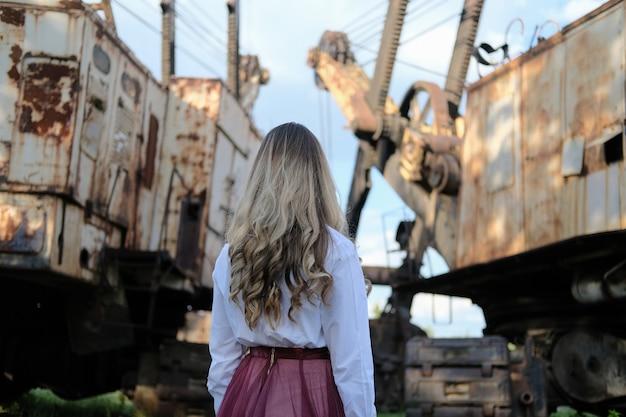 産業景観と古い建設機械の上の美しい少女。グランジスタイルの肖像画。孤独の概念とテクノロジーの世界。