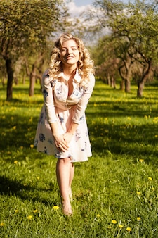 Beautiful young girl in the park in the spring. portrait in full height. vertical photo