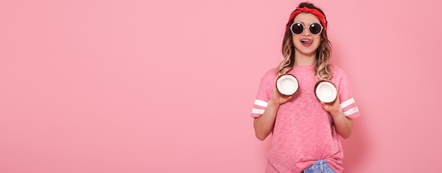 Beautiful young girl in pink t-shirt and glasses holding funny sexy coconuts on pink background