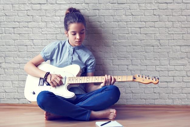 Красивая молодая девушка играет на гитаре