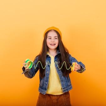 彼女の子供の頃のおもちゃ、虹のスリンキーで遊ぶ美しい少女