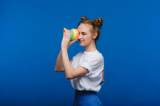 青い壁に虹のセクシーで遊ぶ美しい少女