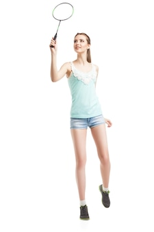 흰색 배경 위에 운동화를 신고 배드민턴 라켓을 가지고 노는 아름다운 소녀
