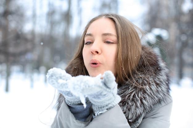 Красивая молодая девушка играет со снегом в парке на зимних каникулах