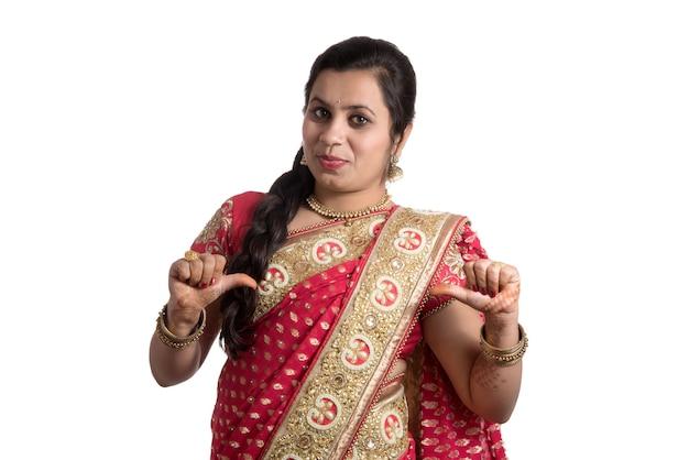 白い壁にインドの伝統的なサリーでポーズをとる美しい少女。
