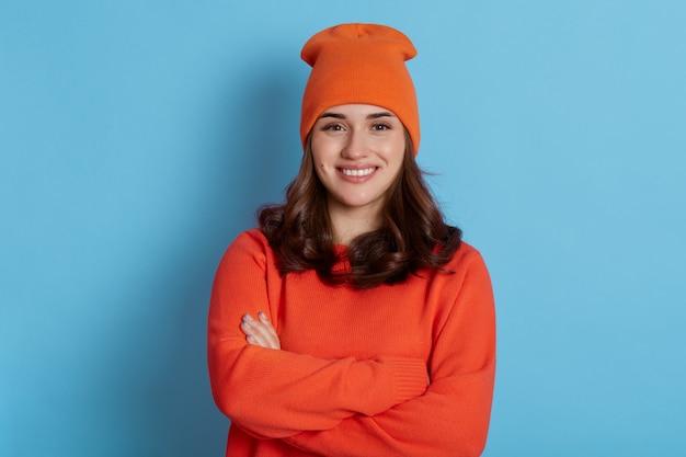 オレンジ色のカジュアルセーターとキャップを身に着けて、腕を組んで魅力的な幸せな笑顔でポーズをとる美しい少女