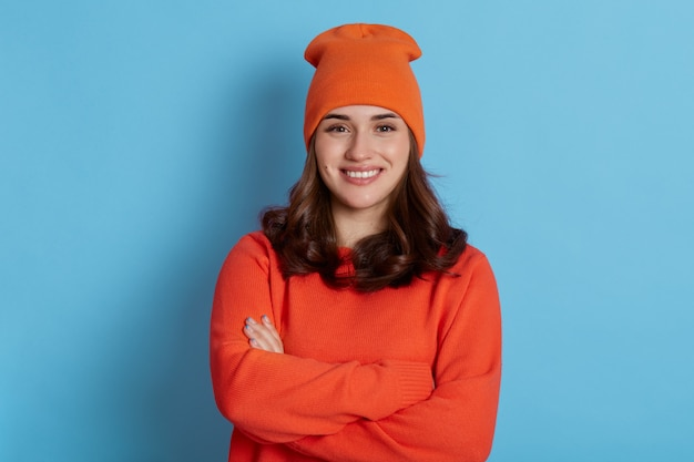 Beautiful young girl posing with folded arms and charming happy smile, wearing orange casual sweater and cap