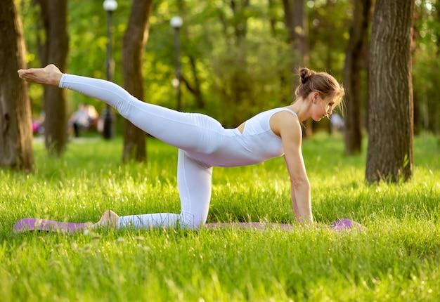 Красивая молодая девушка занимается йогой и отдыхает в гармонии с природой