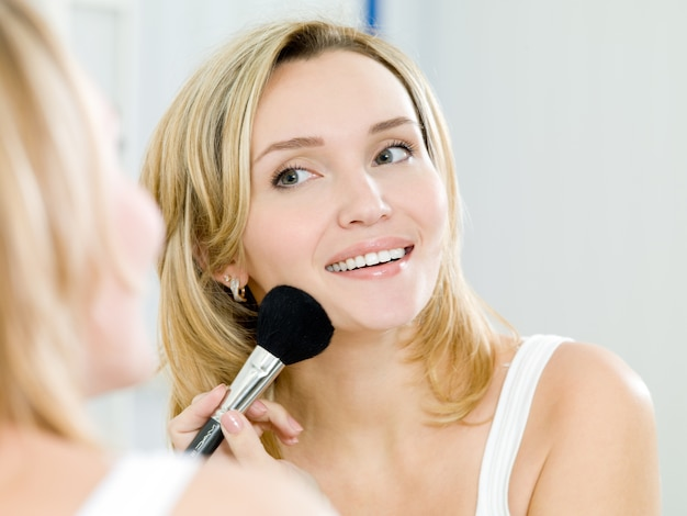 Beautiful young girl puts powder on the face by means of a brush for a make-up - indoors