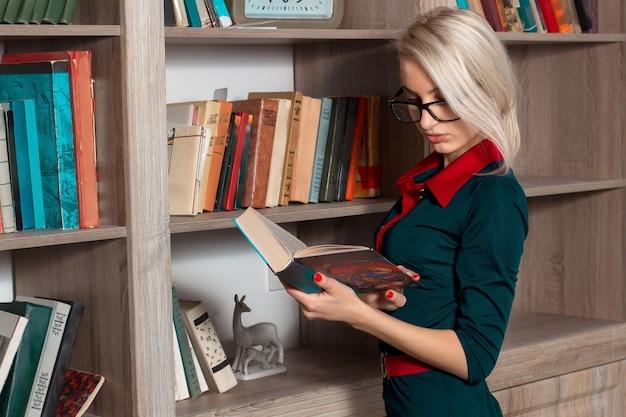 Красивая молодая девушка, читающая книгу в платье
