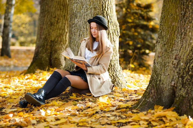 Beautiful young girl reading a book near a tree