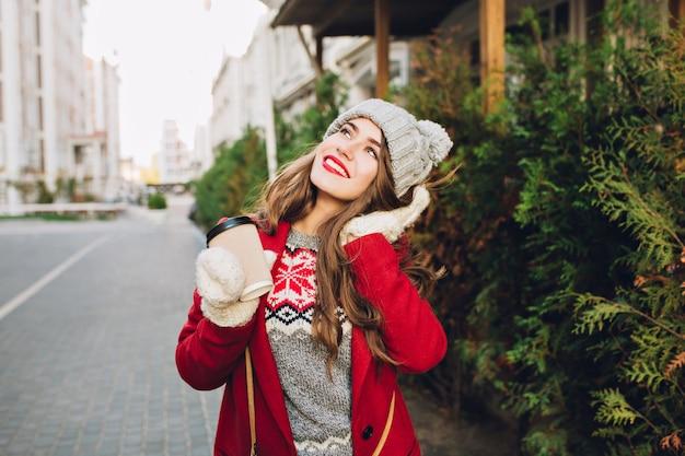 Bella ragazza in cappotto rosso e cappello lavorato a maglia che cammina sulla strada. tiene il caffè per andare in guanti bianchi, sognando il cielo.