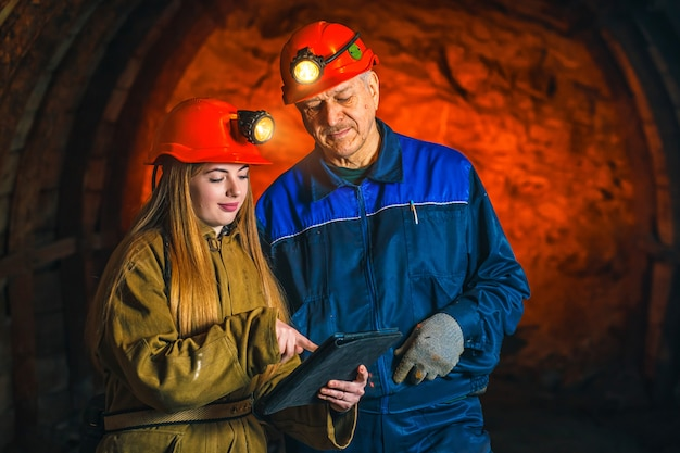 A beautiful young girl in a red helmet and with a tablet in her hands is standing with a miner in a coal mine.