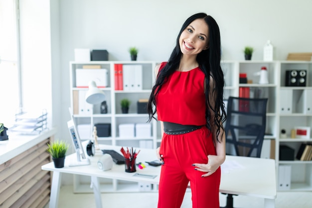 Beautiful young girl in a red suit is standing in the office.