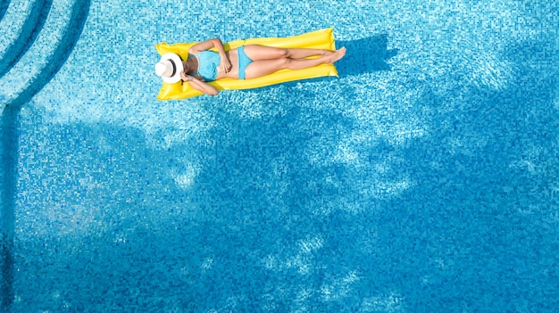 Beautiful young girl relax in swimming pool, woman on inflatable mattress in water, aerial view